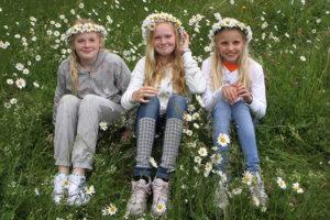 Jenter med blomster i håret under Sankthansfeiringen på Maihaugen, Lillehammer.
