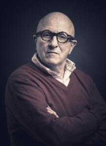 Portrett av Kjell Erik Killi-Olsen med runde briller med kraftig innfatning.