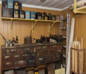Historisk malerverksted med malingsflekkete arbeidsbenk med mange skuffer, malingsspann og annet utstyr.