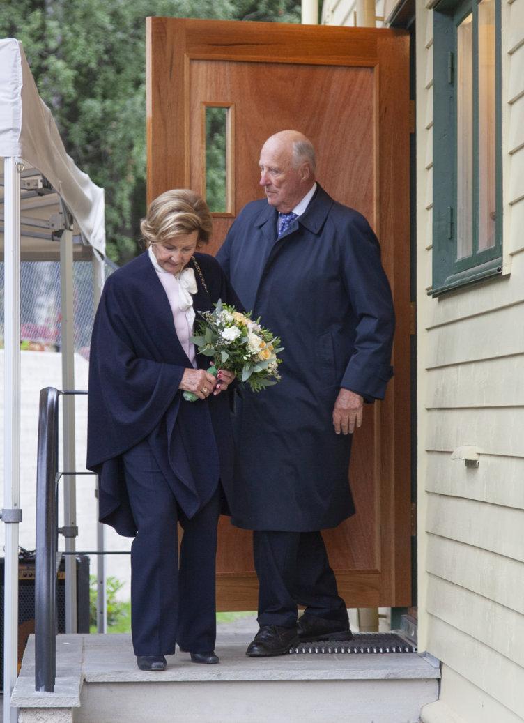 Dronning Sonja og kong Harald på vei ned trappen fra barndomshjemmet hennes.