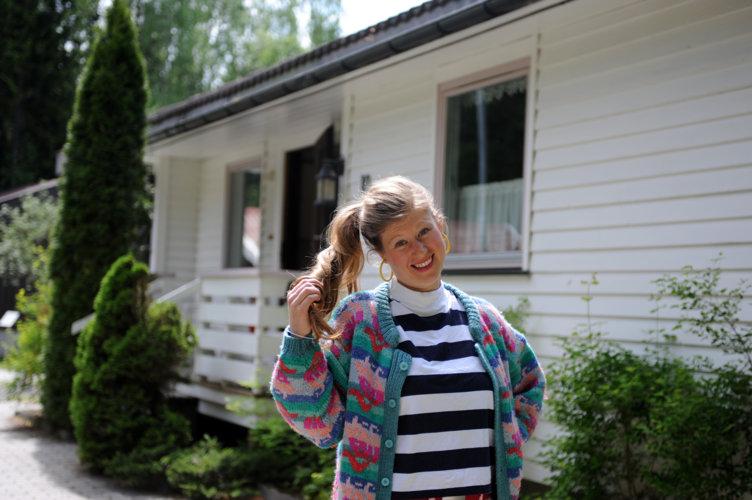 Jente i tidstypiske klær som står foran 80-tallshuset i Boligfeltet på Maihaugen, Lillehammer.