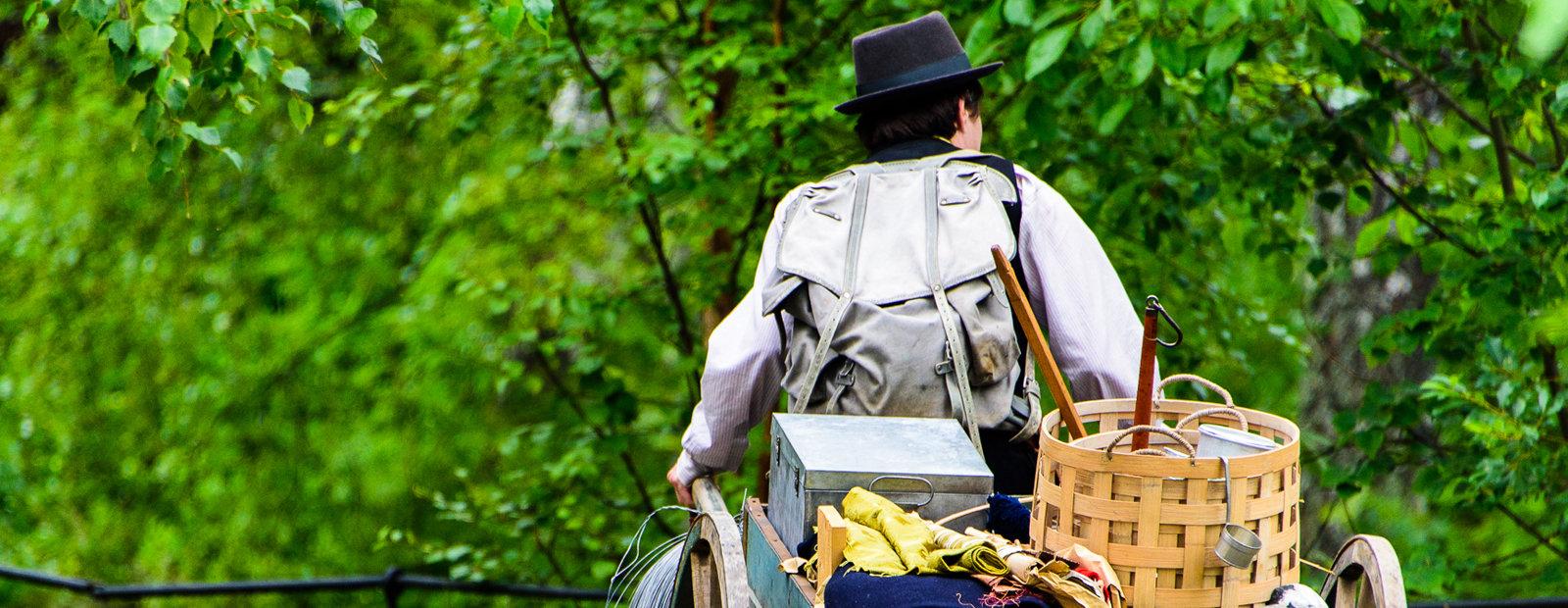 Mann med hatt og sekk trekker en kjerre med saker og ting etter seg på friluftsmuseet Maihaugen på Lillehammer.