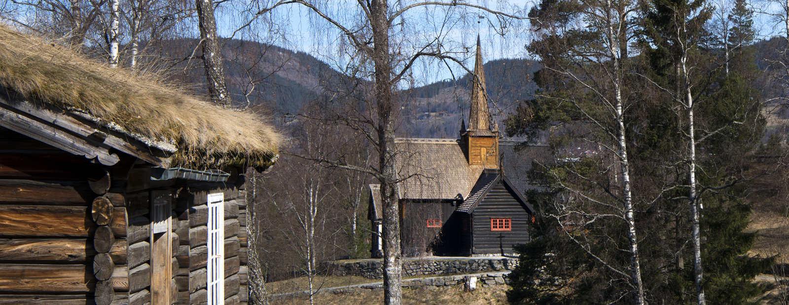 Garmo stavkirke med den gamle skolestua i forgrunnen på friluftsmuseet Maihaugen i Lillehammer.