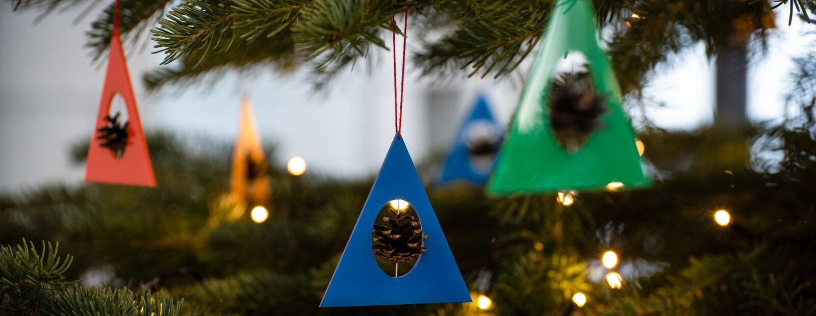 Juletrepynt av farget pleksiglass med furukongler.