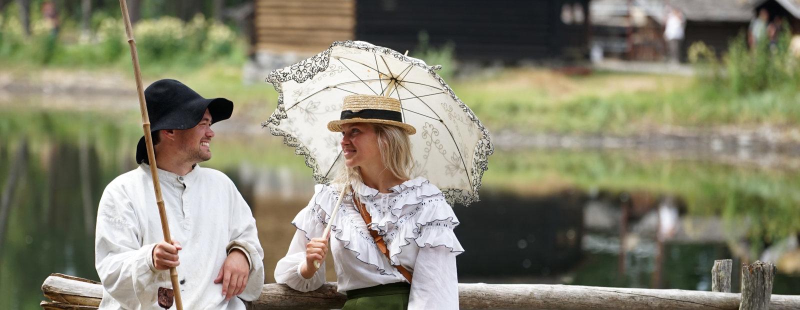 Ung mann med fiskestang og vadmelsklær og en flott pyntet lady med blondeparaply på bru.