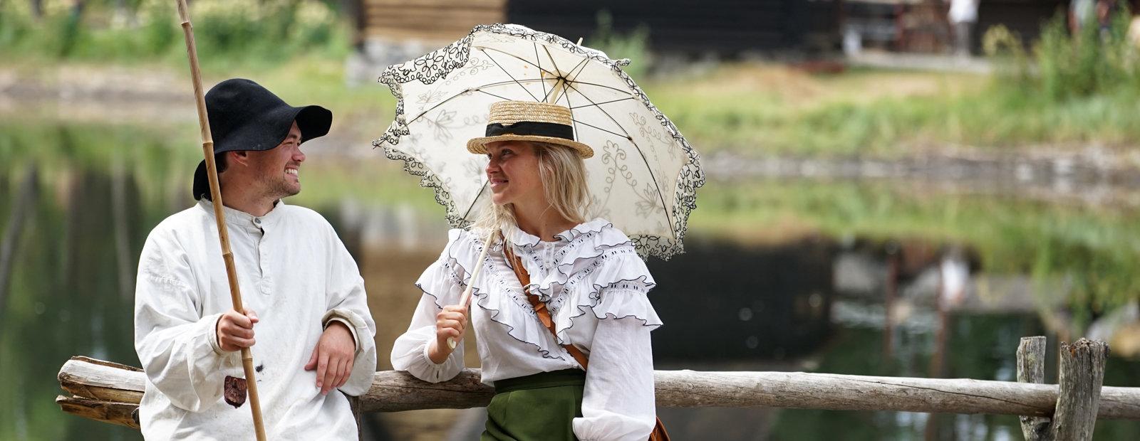 Mann og kvinne i gammeldags antrekk. Mann med fiskestang og kvinne med parasoll.