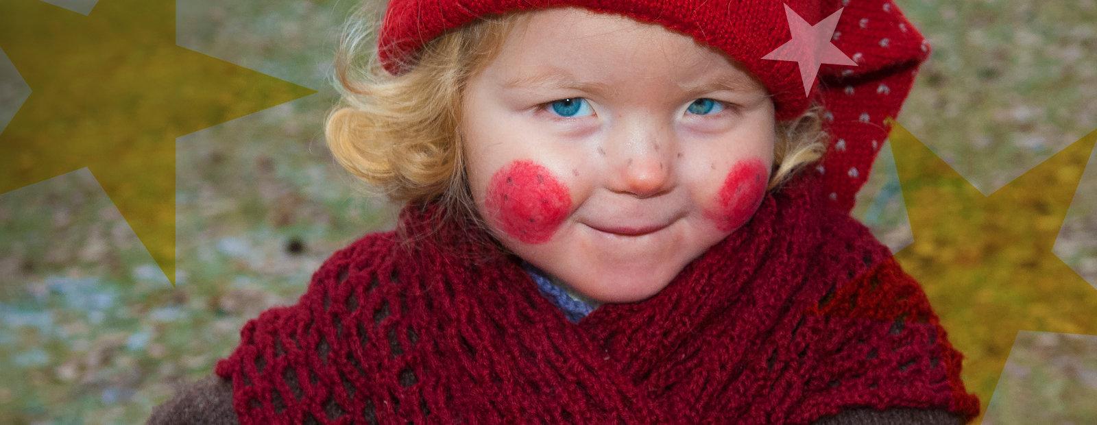 Liten jente med nisselue og røde kinn.