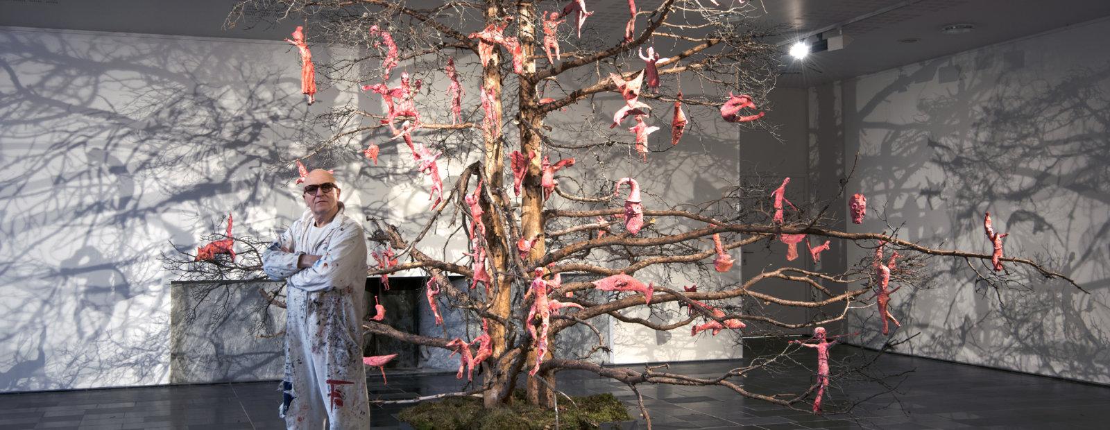 Kjell Erik Killi-Olsen foran en tørr furu dekorert med lyserøde skulpturer.
