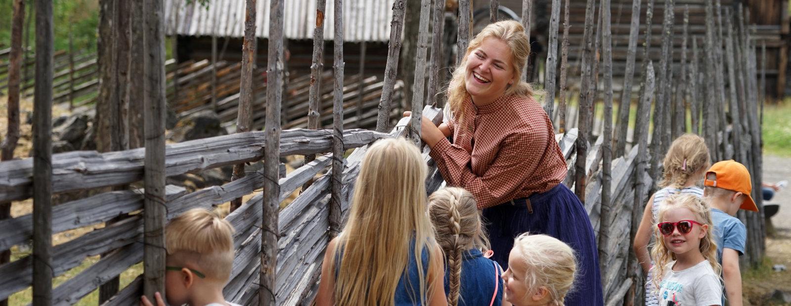 Dame med rutete bluse og forkle står ved skigard og ler med barn.