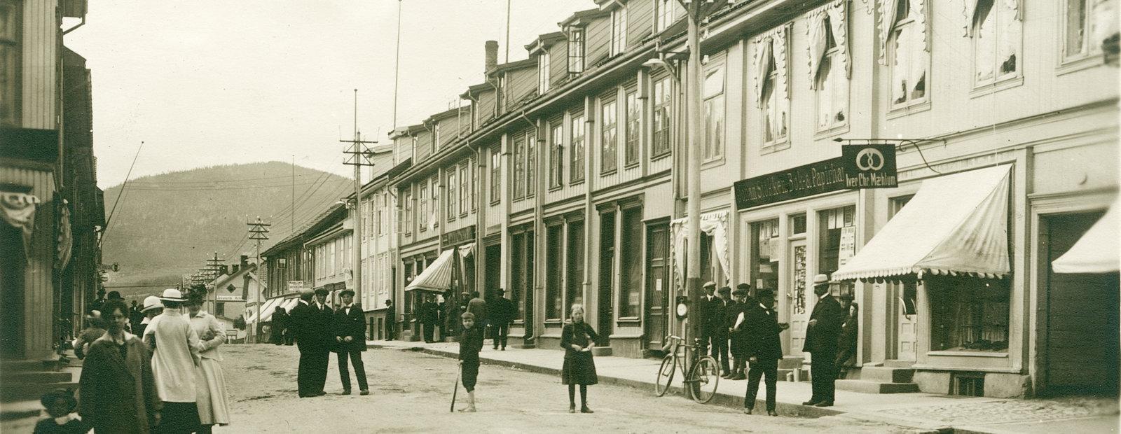 Sort hvitt fotografi med Storgaten i Lillehammer med voksne og barn i gaten.
