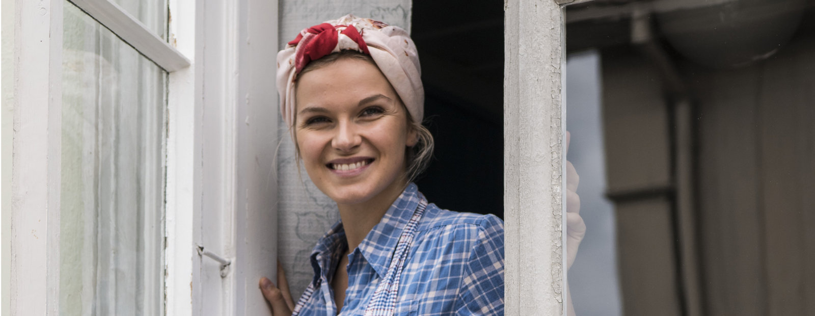 Ung kvinne med tørkle på hodet og blårutete skjorte og forkle titter smilende ut av et hvitmalt vindu.
