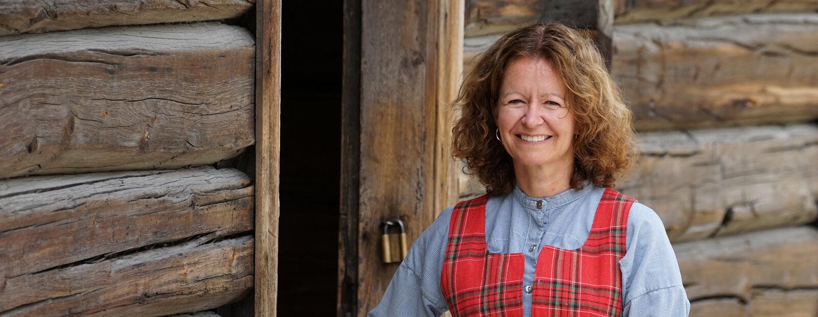 Kvinne med bunad foran tømmerhus på Maihaugen.