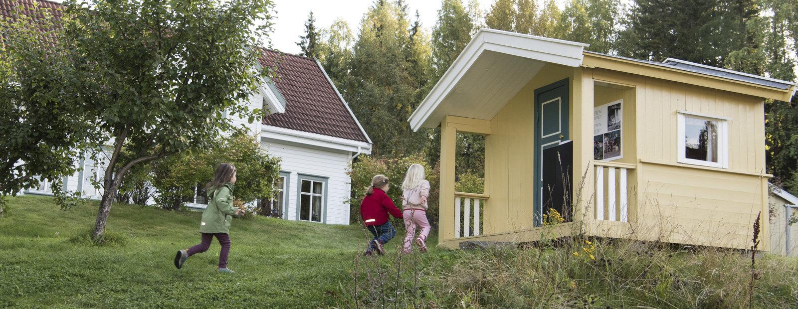 Barn løper mot en gulmalt lekestue fra 1950-tallet i Boligfeltet i friluftsmuseet Maihaugen på Lillehammer.
