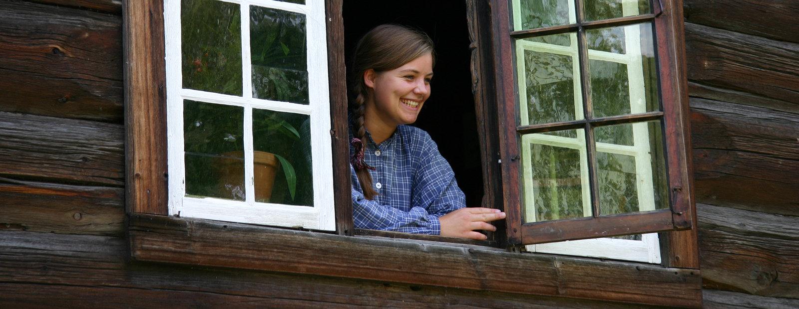 Jente i blårutete bluse kikker ut av vinduet på en historisk tømmerbygning.