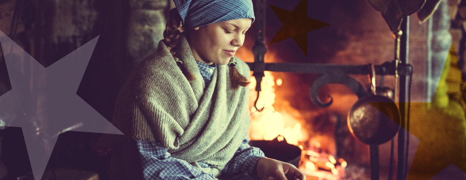 Jente med skaut og sjal ved peisen i Øygarden på Maihaugen.