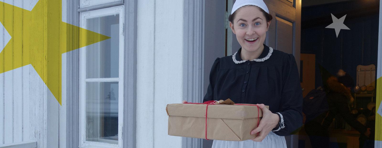 Jente med tjenesteantrekk holder forventningsfullt en pakke med gråpapir og rød hyssing rundt.