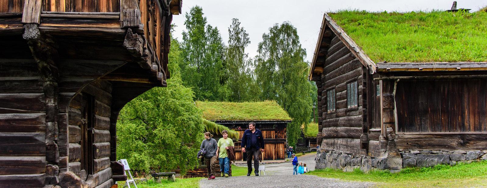 Folk går på grusvei og titter på gamle tømmerhus på friluftsmuseet Maihaugen i Lillehammer.