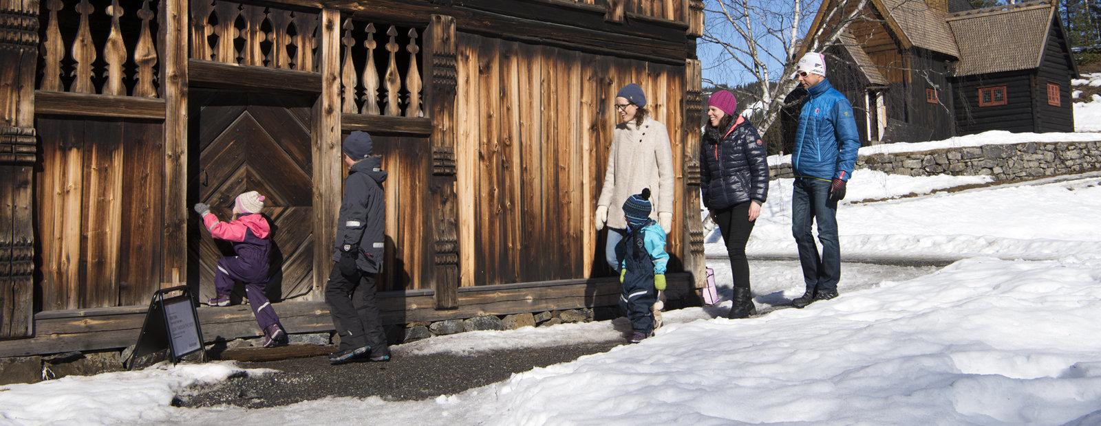 Voksne og barn på vei inn i gammel tømmerbygning med Garmo stavkirke i bakgrunnen. På friluftsmuseet Maihaugen i Lillehammer.