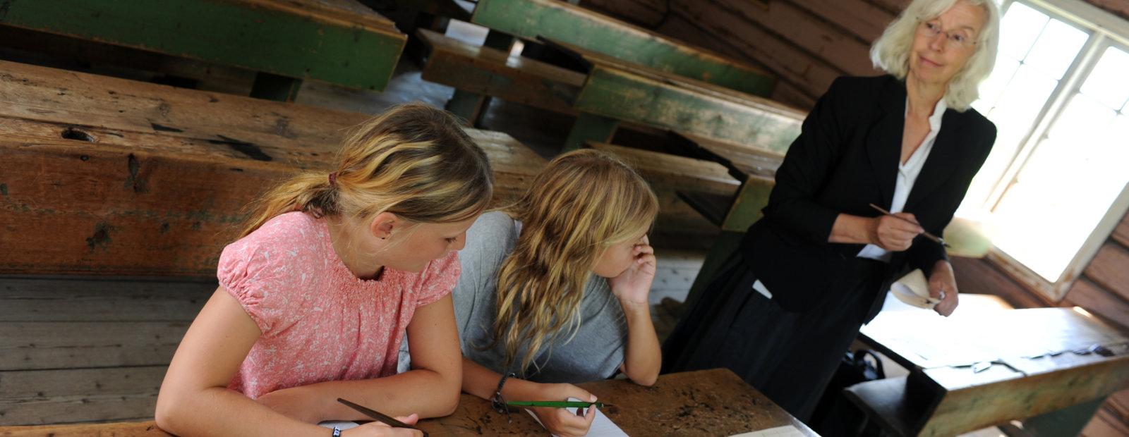 Barna lærer å skrive med blekkpenn i skolestua på Maihaugen