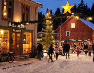 Julepyntet gate med granbargirlander og gule stjerner med juletre i bakgrunnen
