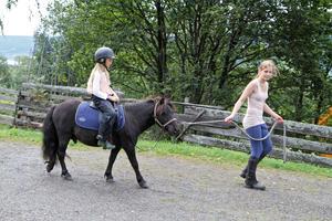 Jente rir på ponni på Barnas sommerdag på Maihaugen, Lillehammer