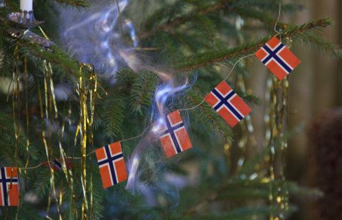 Greiner på et juletre pyntet med norske flagg, englehår, gammeldagse juletrelys av stearin og hengende gullglitter.
