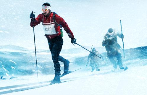 Illustrasjon som viser Kronprins Haakon Magnus i skiklær med startnummer på brystet. Lenger bak følger to Birkebeinere med treski og skinnklær. Illustrasjon: Kristoffer Damskau