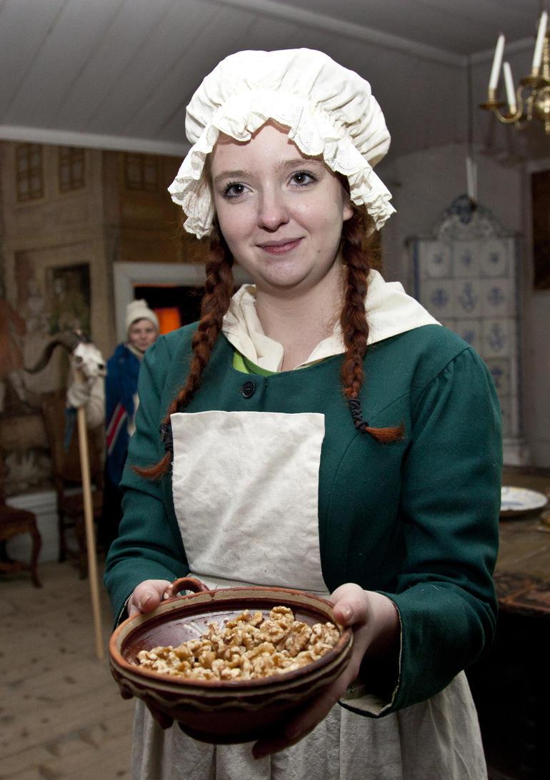 Jente i antrekk fra gamledager rekker fram en skål med nøtter.