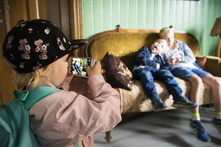 Liten jente tar bilde av to gutter i historisk hus på Maihaugen i Lillehammer