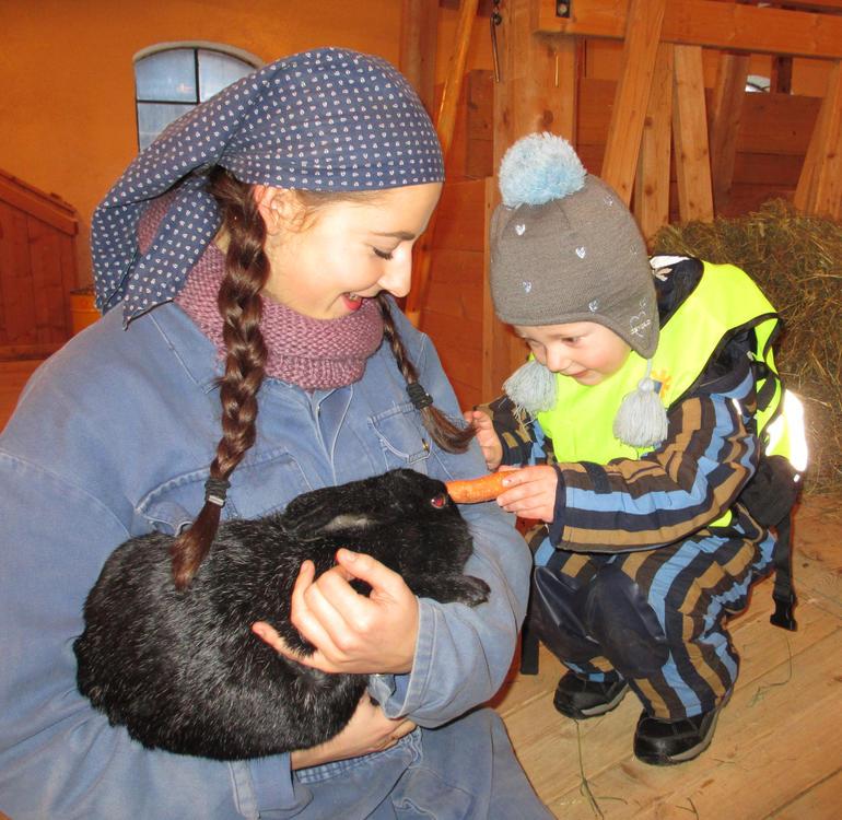 Kvinne med fjøsdress og skaut holder en kanin i armene mens en liten gutt mater kaninen med en gulrot.