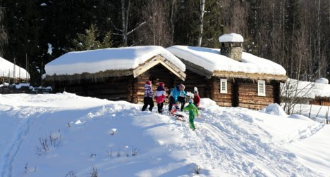 Barn aker foran gammelt tømmerhus på Maihaugen i Lillehammer.