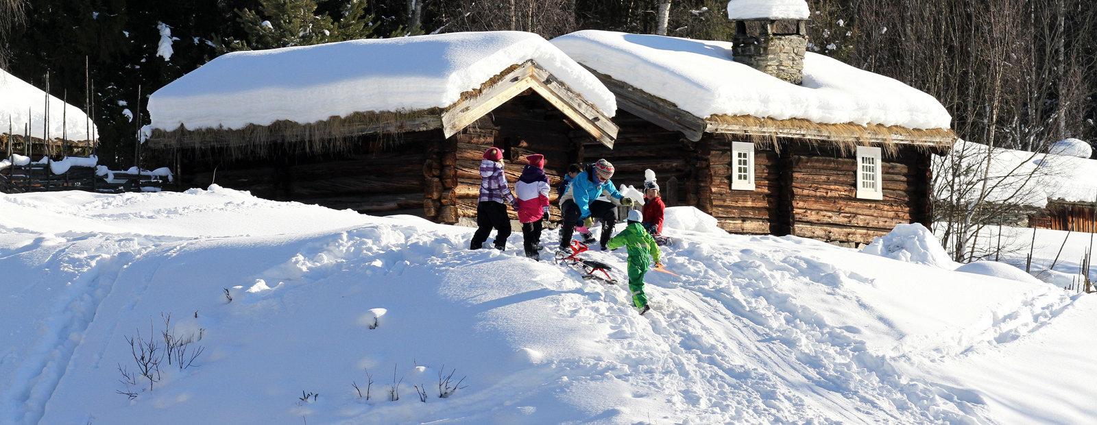 Barn aker foran gammeldags tømmerhus på Maihaugen i Lillehammer.