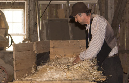 Mann med gammeldagse klær og hatt i arbeid med en gammeldags treskemaskin.