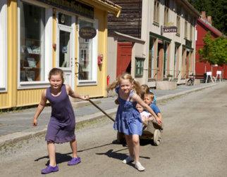 Barn som leker med kjerre i Byen i friluftsmuseet Maihaugen på Lillehammer.