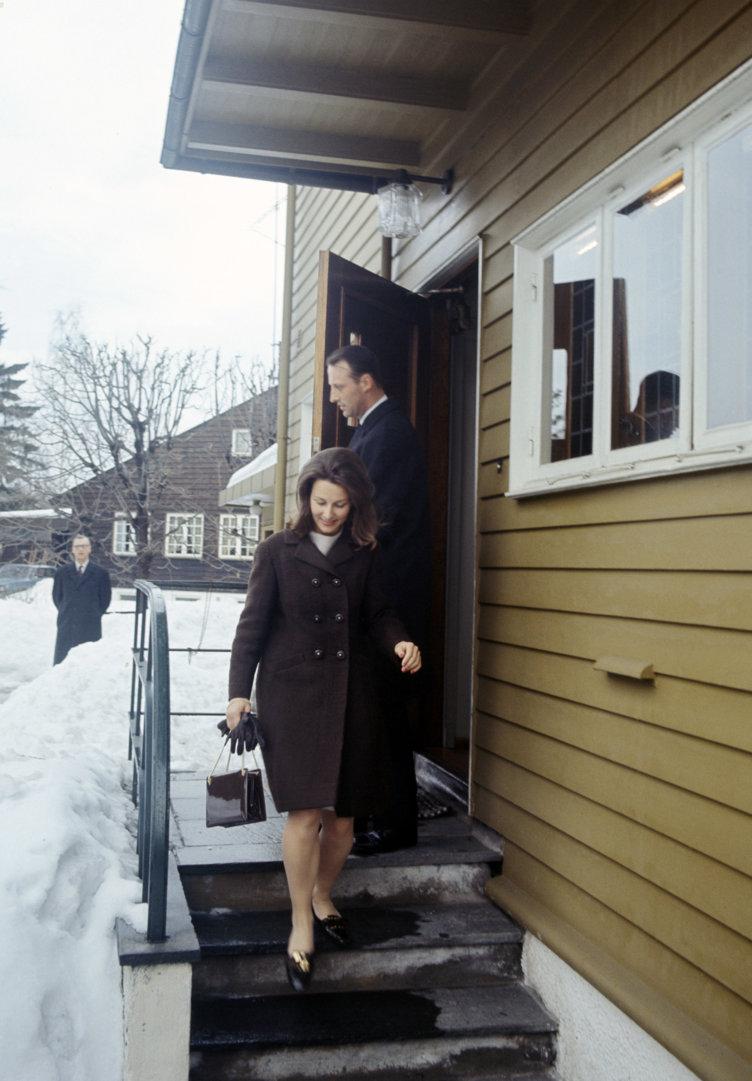 Kronprins Harald og Sonja Haraldsen på trapp utenfor hus.