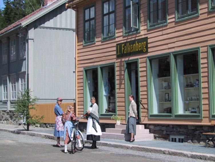 Folk kledd i historiske klær utenfor butikken Falkenberg på Maihaugen, Lillehammer