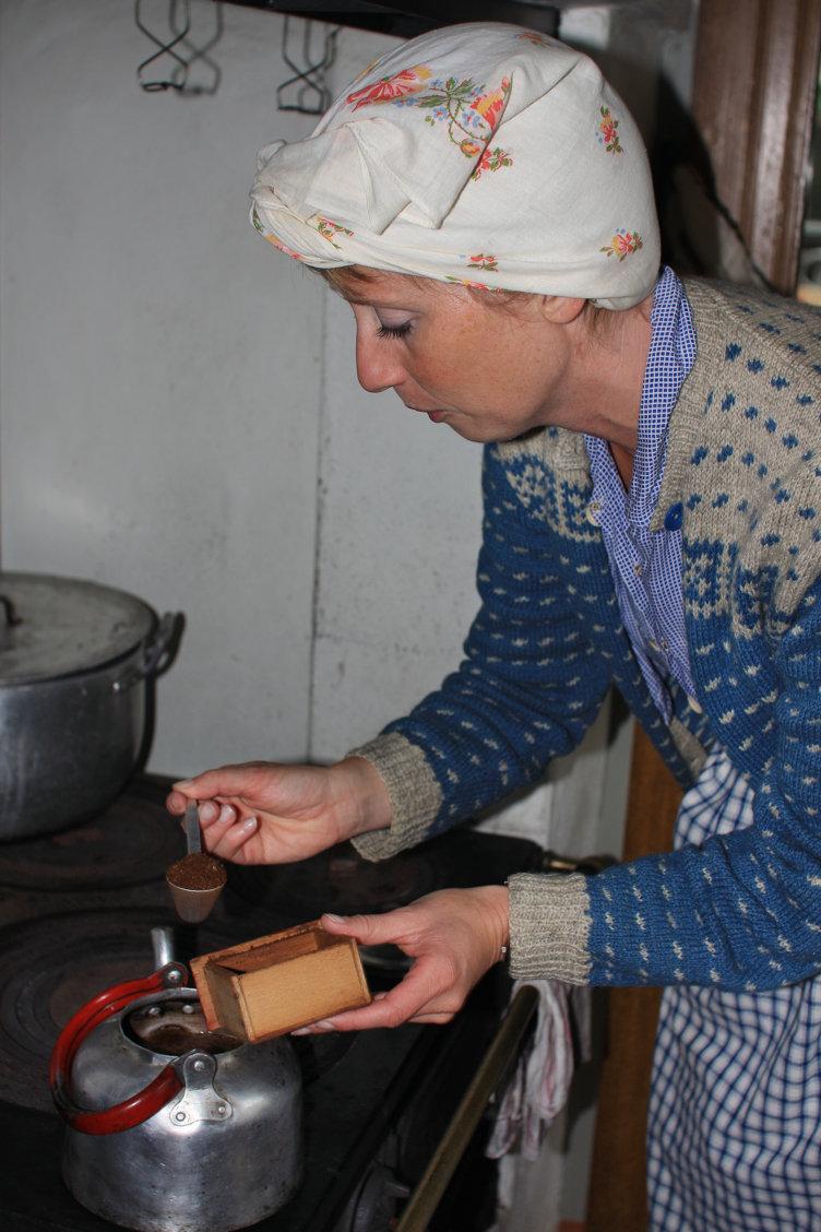 Tidsriktig kledd dame fra mellomkrigsdagene lager kaffe i Olsengården på Maihaugen, Lillehammer.