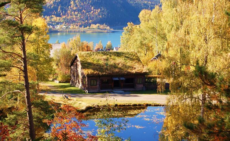 Vakkert høstbilde av gammelt tømmerhus og blankt tjern på Maihaugen.