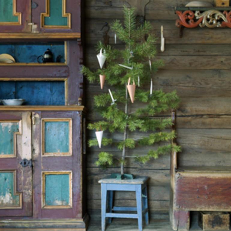 Lite juletre som er enkelt pyntet med noen få juletrelys i stearin og noen få kremmerhus i grått og hvitt papir