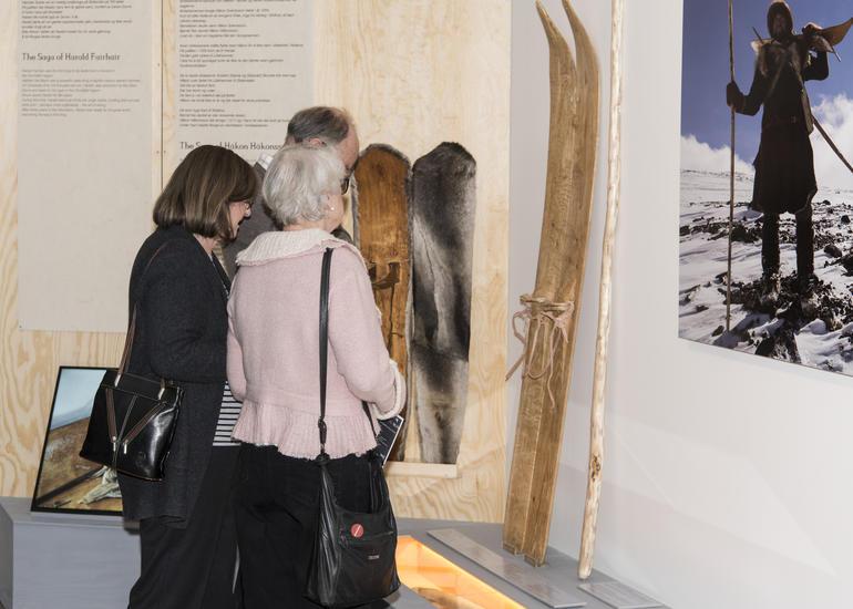 Publikummere studerer gammeldagse ski, det ene paret trukket med pels.