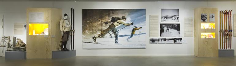 Utstillingslokale med stor illustrasjon på veggen av en kvinnelig skiløper i moderne antrekk som går fra en skiløper med anorakk og gammeldags utstyr. Også flere mindre bilder, montre og gamle ski utstilt.