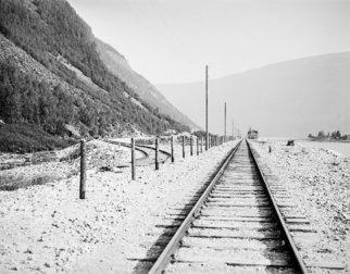 Nærbilde av jernbaneskinner som svinner hen i landskapet.