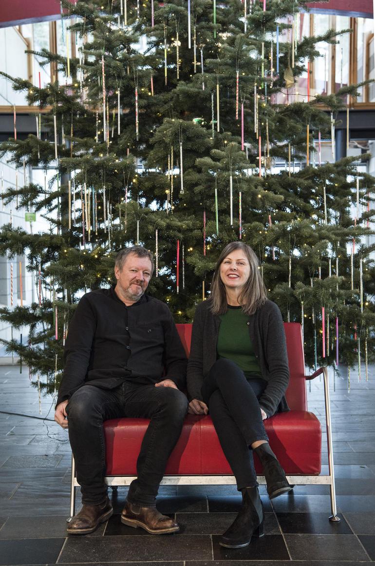 Kjetil Trædahl Thorsen og Jorunn Sannes fra Snøhetta i en rød stol foran et pyntet juletre.
