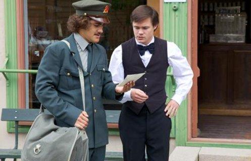 En postmann viser et brev til en mann under et vandreteater på friluftsmuseet Maihaugen i Lillehammer.