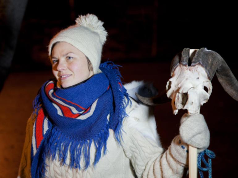 Kvinne med ullklær og lue med som holder en stokk med en hodeskalle med horn fra en geit
