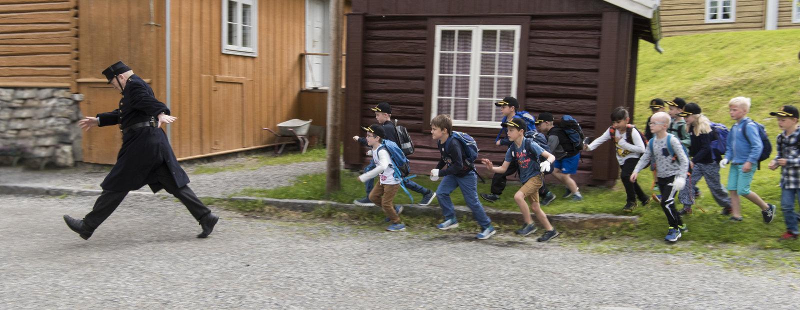 Politimester i gammel uniform går med lange skritt og en gjeng små gutter løper ivrig etter.