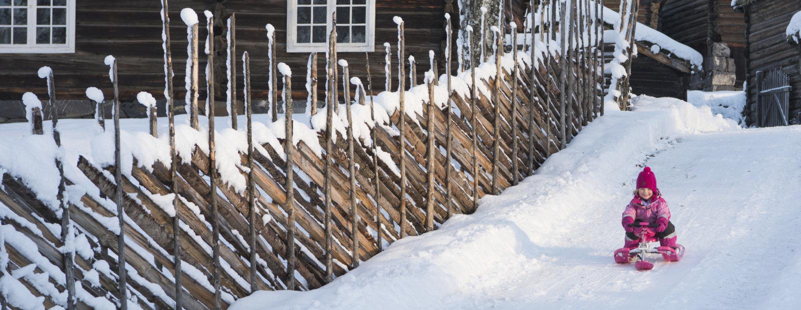 Jente aker på rattkjelke ved siden av en skigard og gammelt tømmerhus.